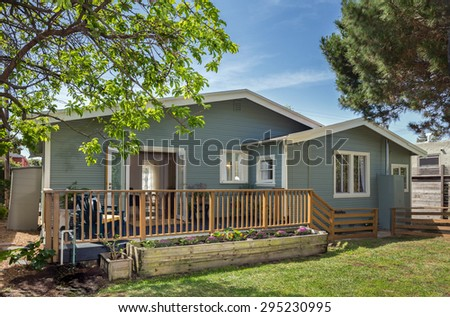Private craftsman home with wooden fence and green yard. - stock photo