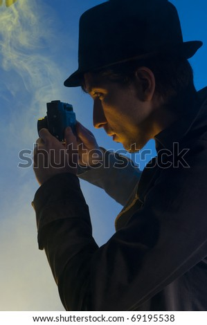 Private detective taking pictures with a small camera, shooted in studio on a blue background with yellow light and smoke - stock photo