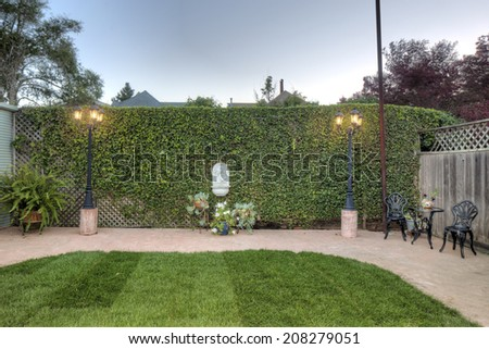 Private green, level fenced yard with sitting arrangement and street lights. - stock photo