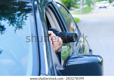 Private investigator on a stakeout is photographing the situation to document the events with a camera sticking out of a car window. - stock photo