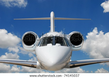 Private jet against blue sky and clouds - stock photo