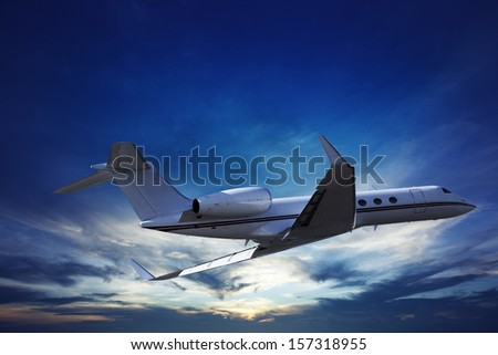 Private jet cruising at sunset - stock photo