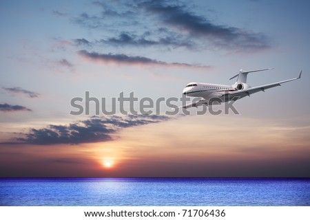 Private jet cruising at sunset - stock photo