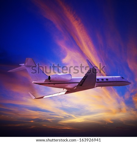 Private jet cruising at sunset. Square composition. - stock photo