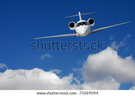 Private jet flying with blue sky and clouds - stock photo