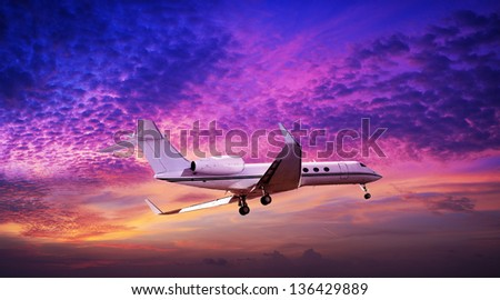 Private jet maneuvering in a spectacular sunset sky - stock photo