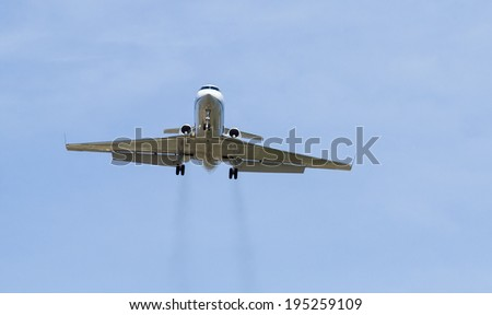 Private jet on landing approach with vapor trails - stock photo