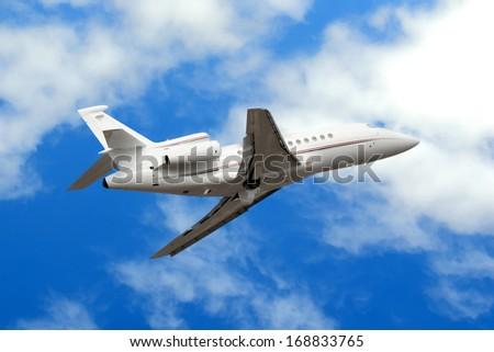 Private jet plane in the blue sky - stock photo