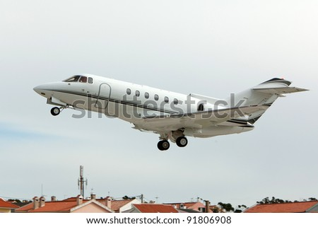 Private jet take-of over roofs - stock photo