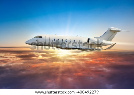 Private jetplane flying above clouds in sunset - stock photo