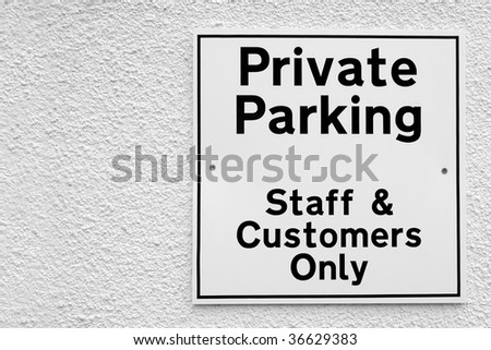private parking sign on a white wall with copy-space - stock photo