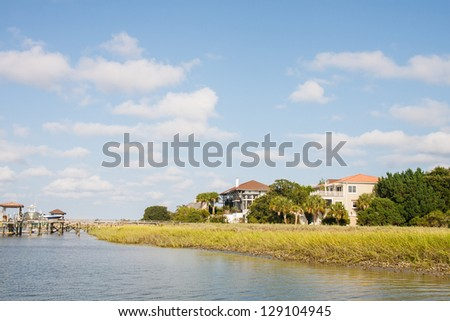 Private pier at Luxury coastal homes on marsh by canal - stock photo