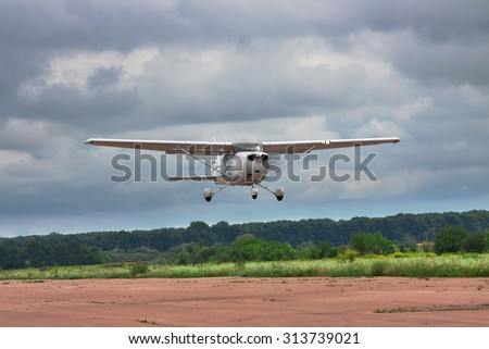 Private plane is taking off into the stormy sky - stock photo