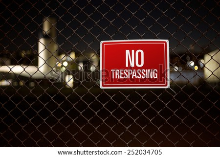Private property behind a chain link fence with red warning sign containing text no trespassing - stock photo