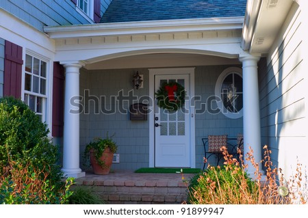 Private residence front porch and entrance adorned with Christmas wreath - stock photo