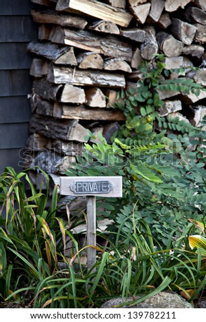 Private sign surrounded by green foliage and a stack of wood.