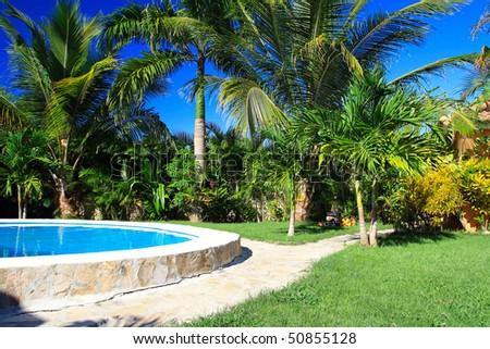 Private swimming pool in Caribbean garden - stock photo