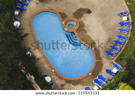 private swimming pool in residential area suburb house aerial view from the top surrounded by green garden and foldable chairs furniture - stock photo