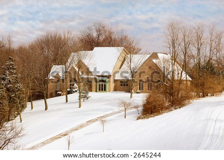 Private two story brick home sitting on a snowy hillside on a cold winter day.