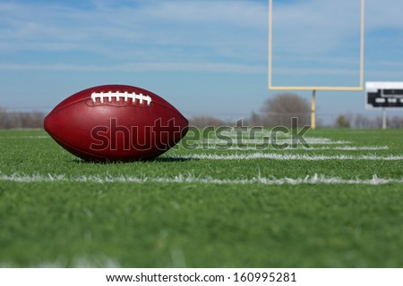 Pro American Football on the Field with Goal Posts Beyond - stock photo