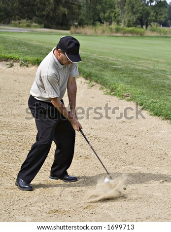 Pro driving the ball from sand trap - ball visible, hovering inches from the club and sand splash - stock photo