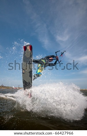 pro-rider kiter makes the difficult jump against the backdrop of the beautiful sky and clouds - stock photo