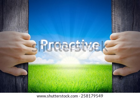 Proactive. Hand opening an old wooden door and found Proactive word floating over green field and bright blue Sky Sunrise. - stock photo