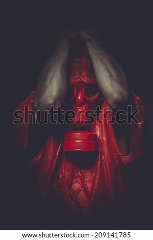 Problem, A man in a gas mask over  the smoke. black background and red colors - stock photo