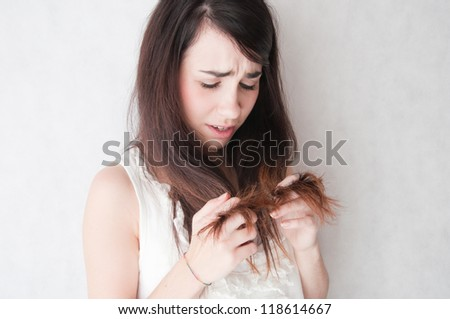 Problem with hair. Young woman worriedly looks at the tangled hair.
