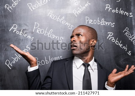 Problems all around me. Depressed African man in formalwear standing against blackboard with inscription Problems and gesturing