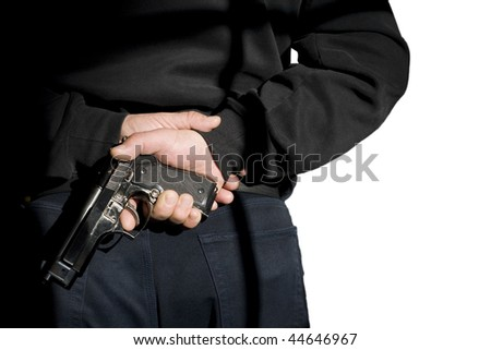 Problems of terrorism and the unauthorized application of shooting iron. Person holds(hide) a handgun behind a back. Shadow on a back. - stock photo