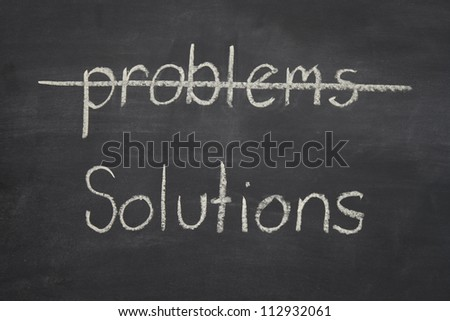problems - solutions written on a blackboard / chalkboard with the word problems crossed out, and solutions underlined.
