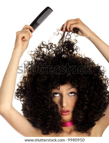 problems with hair. woman with thick hair and comb.  Woman wearing a huge afro wig. Model in a big afro wig. - stock photo