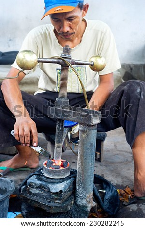 PROBOLINGO, INDONESIA- APRIL 22, 2012: Unedentified  Indonesian man repairs motorcycle inner tube - stock photo