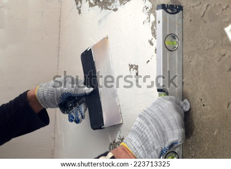 Process fillers and leveling concrete gray wall with a spatula and the water level - stock photo