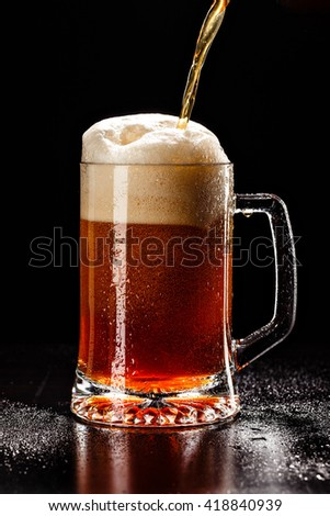 Process filling Beer Glass with DROPS on black. FRESH! MUCH FOAM! Beer bubbles closeup. DRAFT. Overflow beer glass. Glass of alcohol. Closeup Cold Beer. Pint of beer. Good for brewery commercial - stock photo