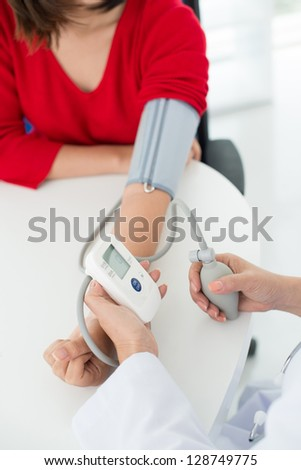 Process of blood pressure measuring in hospital - stock photo