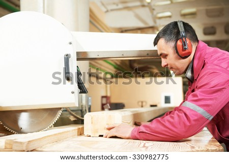 process of carpenter worker with circular saw machine at wood beam cross cutting during furniture manufacture - stock photo
