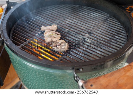 process of cooking delicious chicken gizzards - raw fresh chicken gizzards on gridiron - stock photo