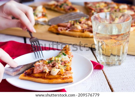 process of eating pizza with sausage, chicken, corn and cheese
