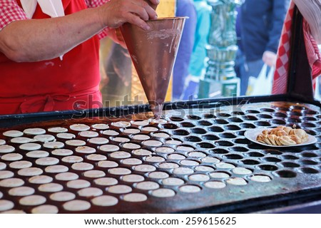 Process of making Dutch pancakes - poffertjes - stock photo