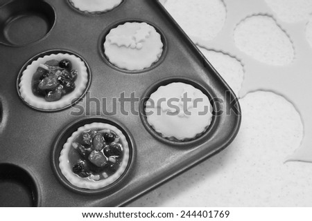 Process of making mince pies with pastry and traditional mincemeat filling - monochrome processing