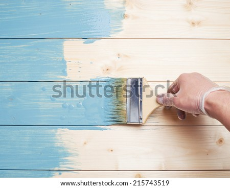Process of painting the pine wood boards with the brush and the blue paint - stock photo