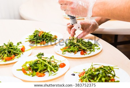 Process of preparing sauce for salad, at kitchen. Man pouring sauce into plate with salad ingredients