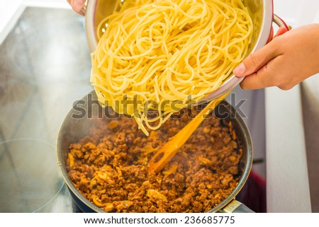 Process of preparing spaghetti Bolognese through the stages. Mixing minced meat in frying pan with vegetables. - stock photo