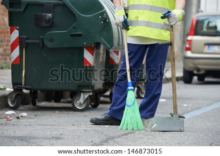 Process of urban street cleaning sweeping. Worker with broom and dust pan - stock photo