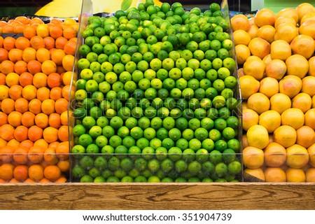 Produce market display of fresh limes, grapefruit and oranges - stock photo