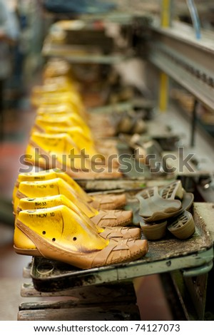 Production line in a footwear factory, half finished shoes on lasts - stock photo