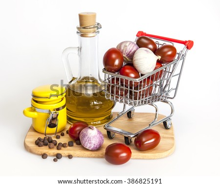 Products and kitchen utensils for cooking of seasoning from garlic and tomatoes. Cherry tomatoes in the cart for purchases - stock photo