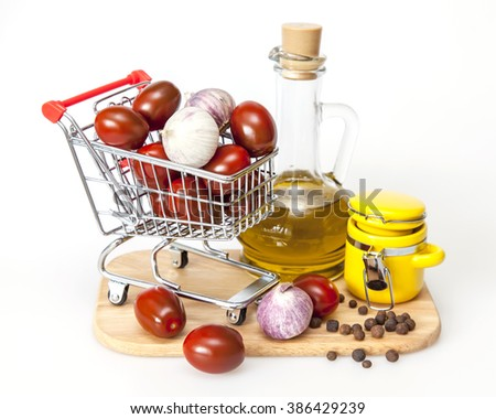 Products and kitchen utensils for cooking of seasoning from garlick and tomatoes. Cherry tomatoes in the cart for purchases - stock photo